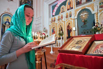 Девушка читает молитву в православном храме